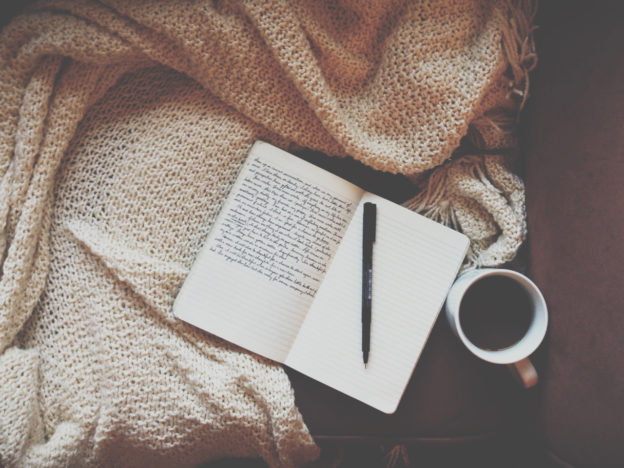 A journal is laying open on top of a blanket. There is writing on the left page of the journal and there is a pen sitting on the right page. There is a mug full of coffee to the right of the journal.